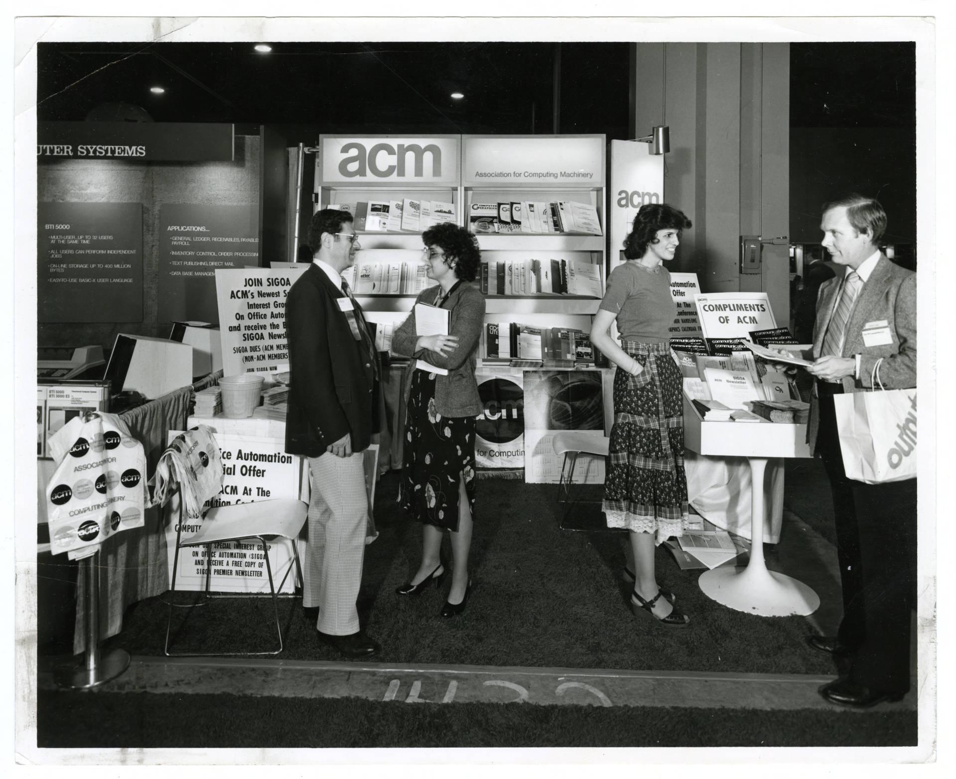 Imagem preto e branco que descreve pessoas conversando em uma Cabine de produtos da ACM em 1978